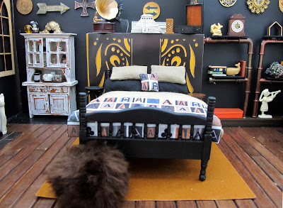 One-twelfth scale miniature scene, with a bed dressed in linen and black with throw rug and cushion printed with letter As, in front of a false wall. To the left of the bed is a distressed dresser and to the right is a set of pipe shelves.