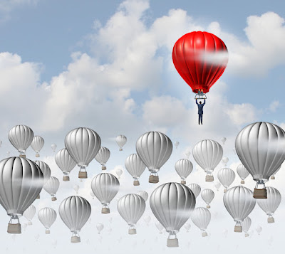 One red hot air balloon rises above all the others colored grey