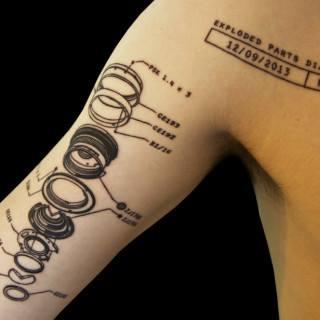 Tatuaje partes del objetivo fotográfico en el interior del brazo