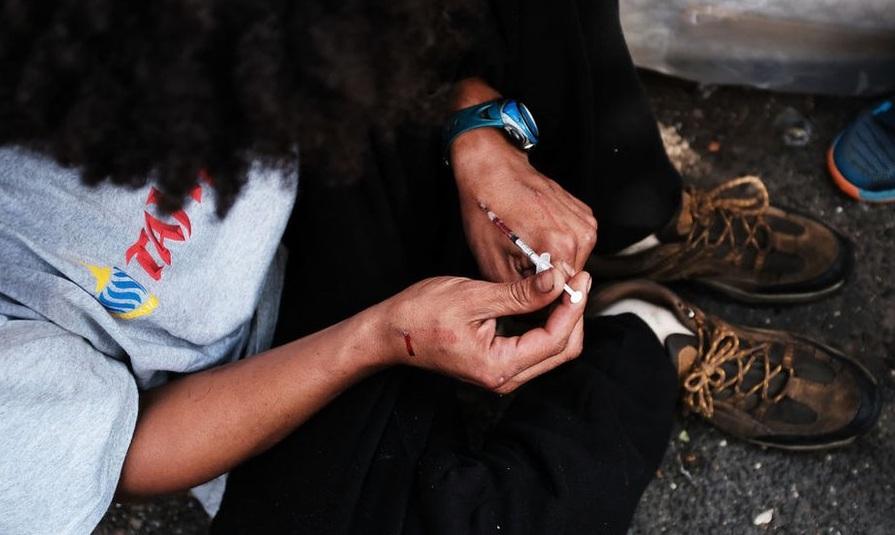 Seorang pemadat menyuntikkan heroin salah satu jenis opioid di jalanan South Bronx, New York. Diperkirakan sekitar 2,4 juta warga AS kecanduan obat-obatan tersebut