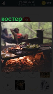 на костре жарится сковородка с едой и рядом сидят двое парней в ожидании