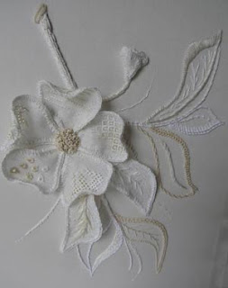 embroidered magnolia flower applied to an embroidered background with leaves