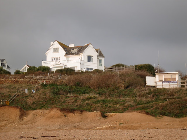 White house on top of hill, coast guard hut nearer beach - with black sky beyond.