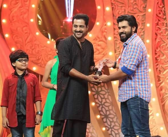 Kishore Satya receiving best actor award for his performance in Karutha Muthu serial from actor Nivin Pauly