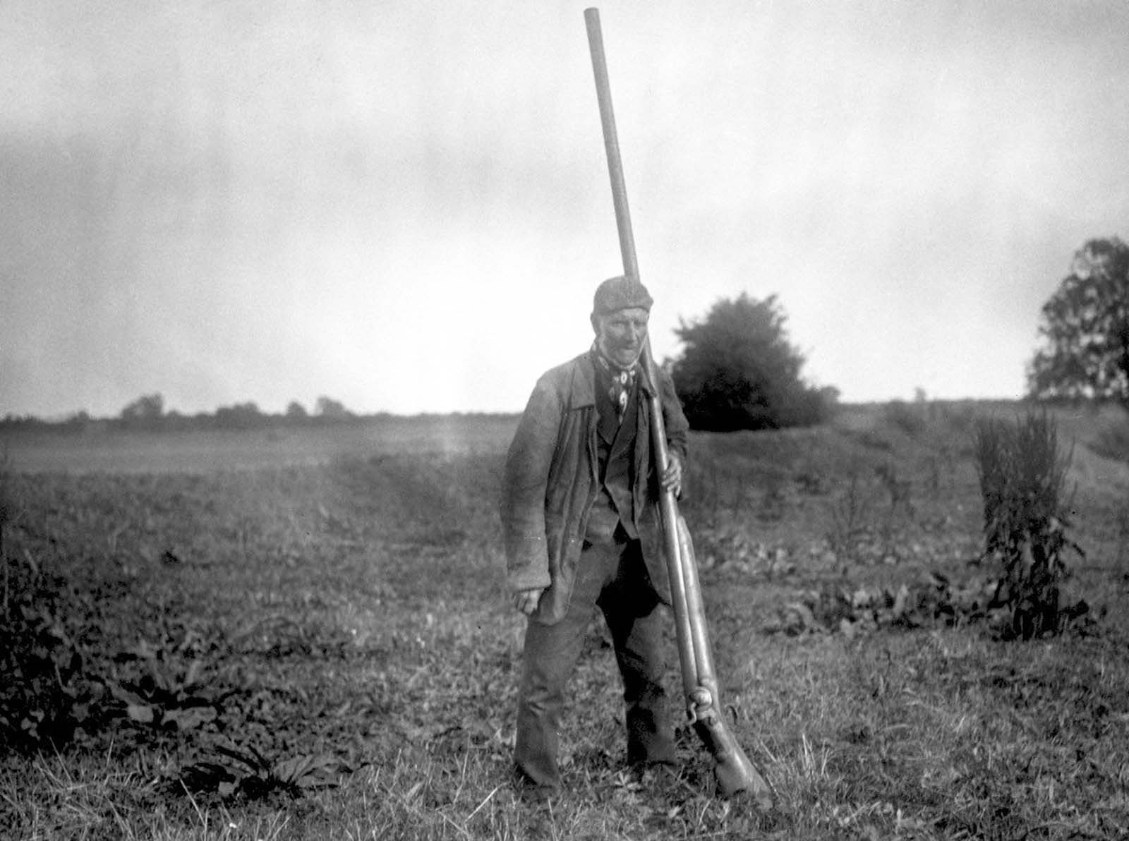 Size comparison of a man and punt gun. 1910.