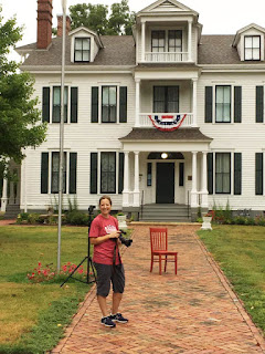 Female photographer in red shirt and black capris posing in front of a red chair on the brick sidewalk in front of a historic two-story mansion