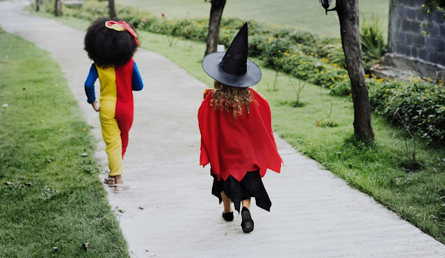 Two children in fancy dress walking away down a path