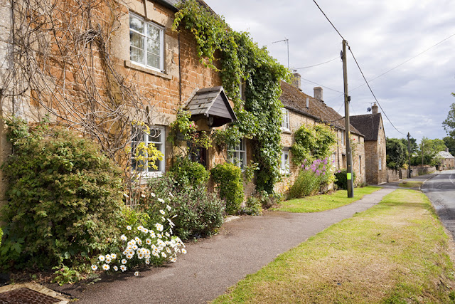 Plants cover the front of a cottage in Kingham Oxfordshire by Martyn Ferry Photography