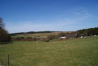 Ein Blick in die Eifellandschaft. Im Hintergrund ein kleiner Hof.