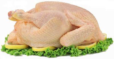 Cómo elegir los pollos. Pollo crudo sobre hojas de lechuga y rodajas de limón