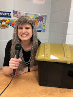 Children's Librarian Wearing a Silver Wig and Talking into a Microphone