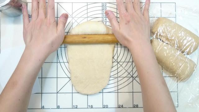 以擀麵棍把麵糰壓長並壓出空氣