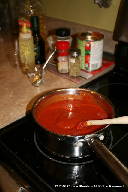 Pizza sauce in a pan warmed on the stove.