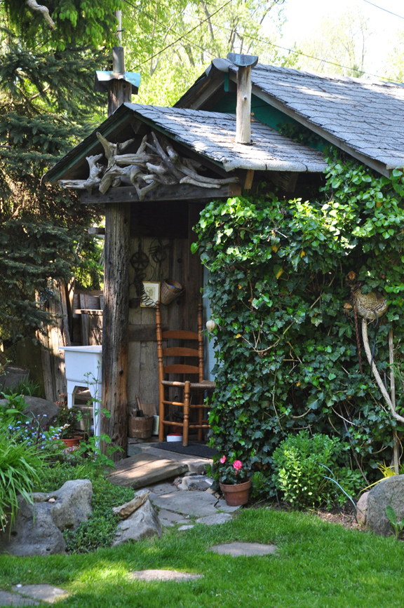Three dogs in a garden garden sheds everything from for Rustic shed with porch