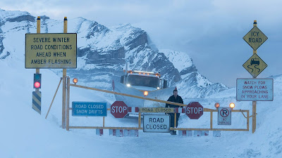 Severe weather signs and road closures in a snowstorm from the movie Cold Pursuit