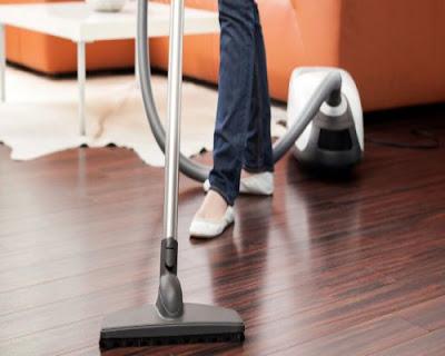 Dùng máy hút bụi làm sạch bề mặt sàn gỗ tự nhiên