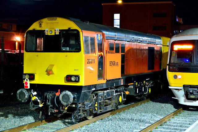 Night photograph of HNRail Class 20311 pauses at Banbury station whilst transporting new London Underground coaching stock.