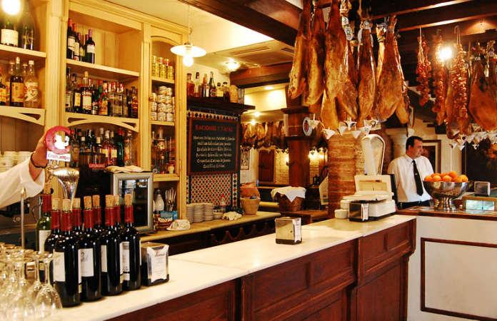 Interior de Casa Román, barra del bar de tapas y un camarero