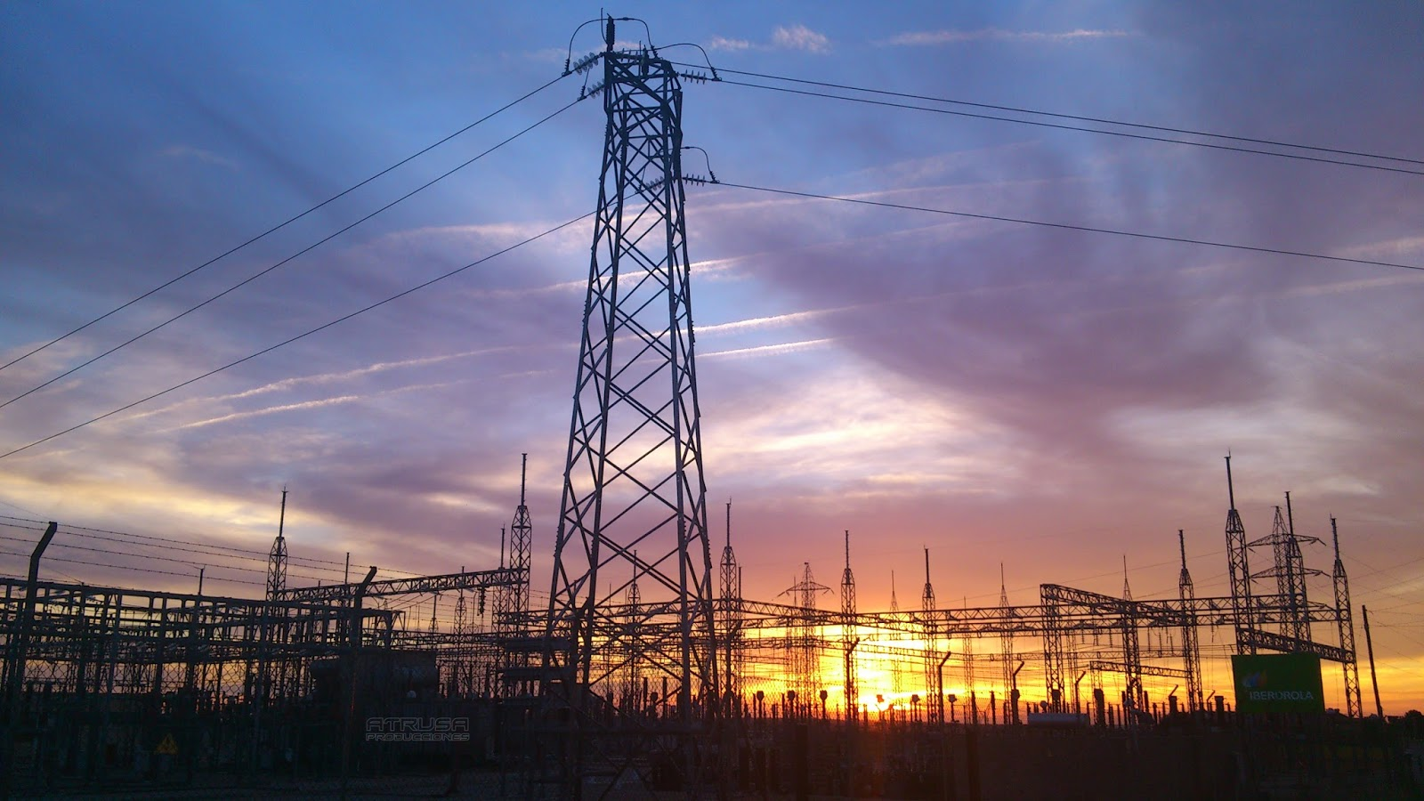 Central eléctrica con puesta de Sol de fondo