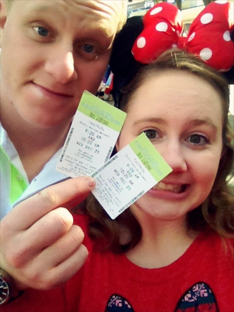 Couple selfie holding paper fastpasses at Magic Kingdom