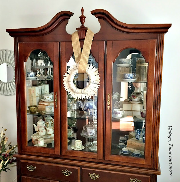 paper wreath with burlap ribbon on china hutch
