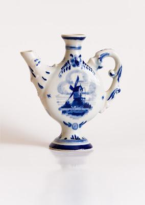 A small blue delft jug with a windmill design.