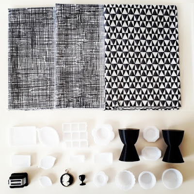 Flat lay of black and white items including fabric pieces, a one-twelfth scale modern miniature toaster, white platters, black Philippe Starck Prince Aha stools, a cameo and a black wine goblet