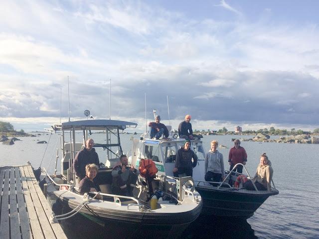 Kaksi venettä laiturissa, 9 ihmistä.