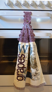 A hand towel hangs from the crossbar handle of a kitchen stove. The towel is made from a folded tea towel and a crocheted top is attached which buttons over the handle. The crocheted top is purple to match the coloured text on the tea towel which says 'grapes'.