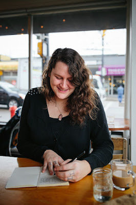 A dark haired woman in a black shirt writing in a notebook while sitting at a table in a restaurant.