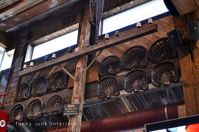 Antique tractor seat collection hung as wall art on wood wall at Mission Springs Brewing Company, a junk-filled pub and restaurant.