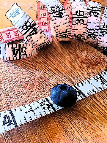 Tape measure with blueberry on cutting board