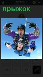 На парашюте мужчина с женщиной совершают прыжок вместе, показывая жестами свое удовольствие