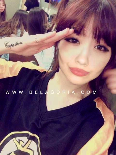 Foto de una chica japonesa haciendo saludo militar, vemos en su mano tatuaje de carpe diem