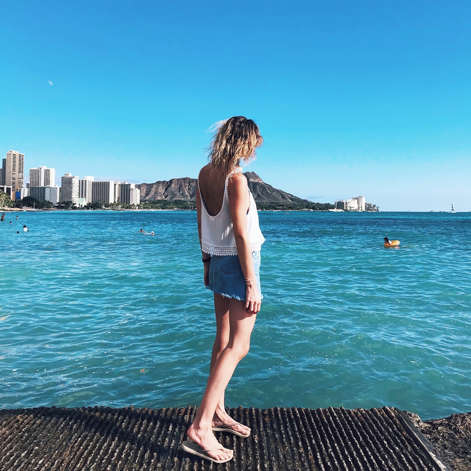 fashion and travel blogger, Alison Hutchinson, at beautiful waikiki beach in Honolulu, Hawaii
