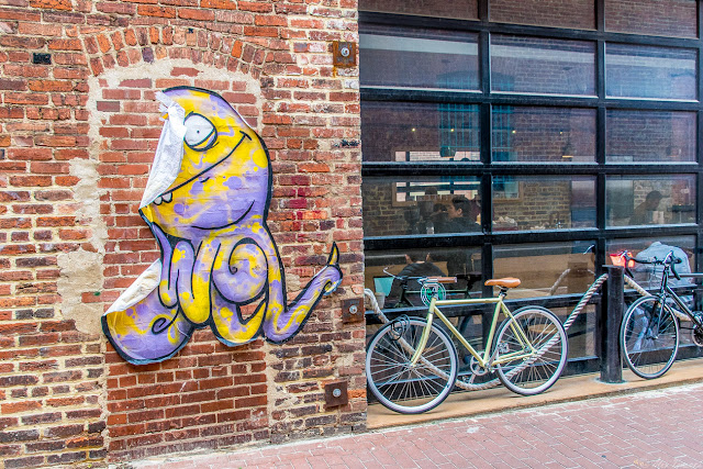A peeling alien mural outside of a coffee shop down in Blagden Alley in Washington, DC.