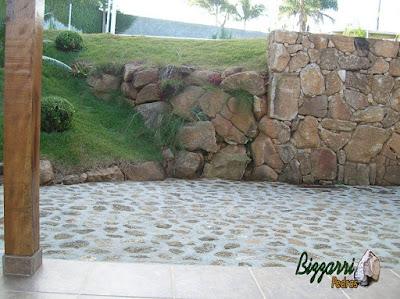 Detalhe do acabamento do canto do muro de pedra faceado e no início do talude o muro de pedra sem cimento com nichos para colocação de plantas com o piso de pedra bruta.