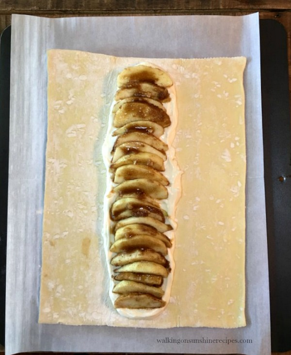 Layer the sliced apples on top of the cream cheese mixture for the Apple Braid Recipe from Walking on Sunshine Recipes