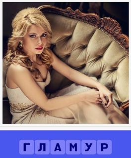 на диване сидит гламурная девушка в платье с длинными волосами