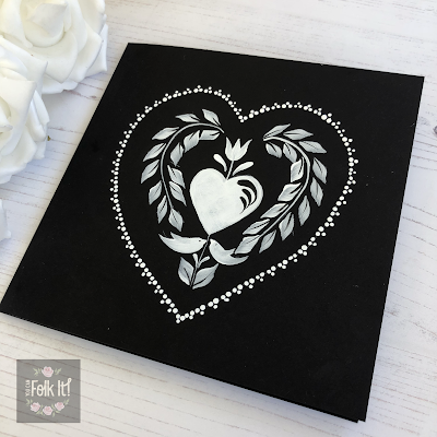 Black card painted with a traditional folk art design created by Carol Sykes from You Can Folk It next to some white roses