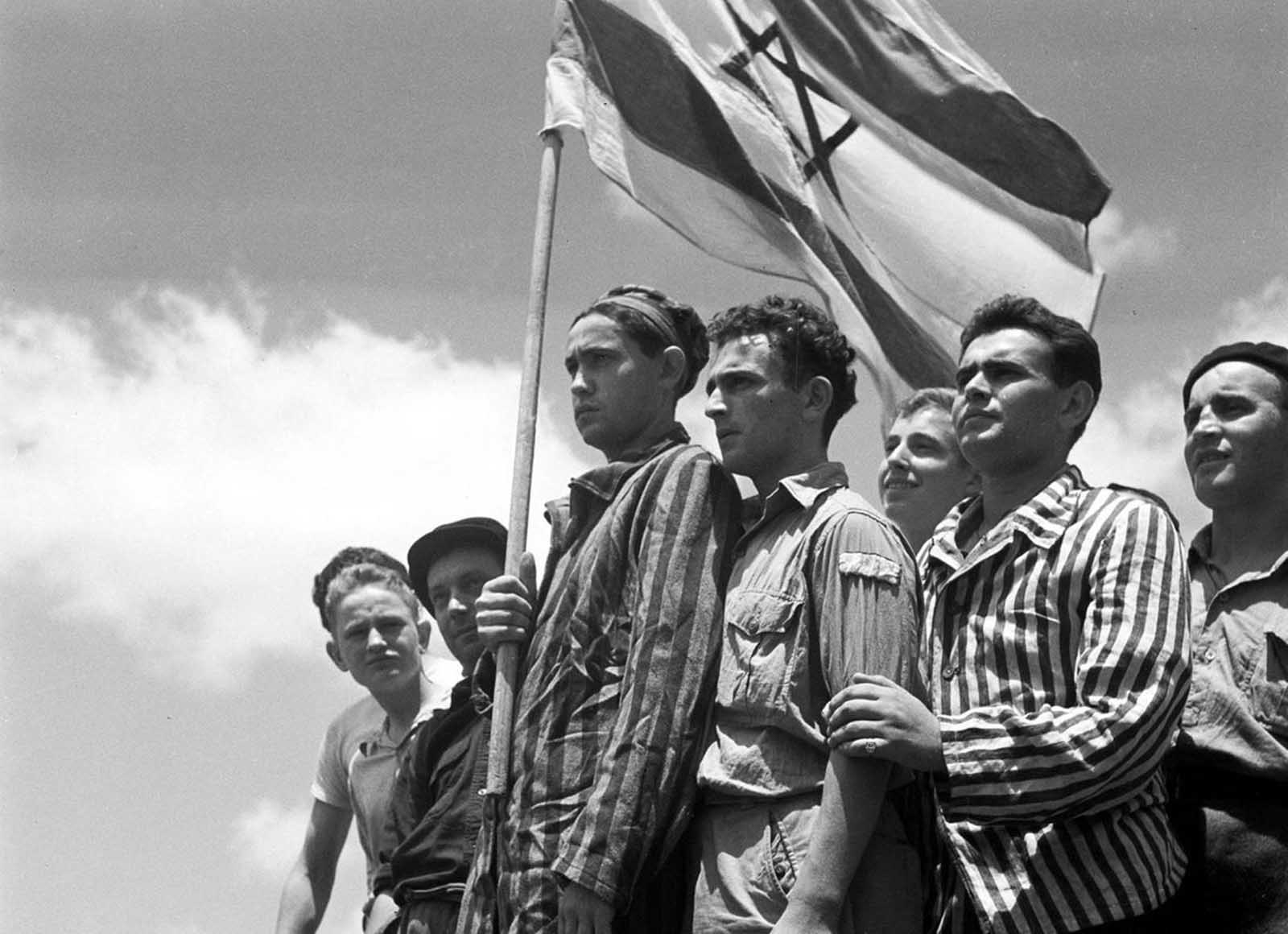 Jewish survivors of the Buchenwald Nazi concentration camp, some still in their camp clothing, stand on the deck of the refugee immigration ship Mataroa, on July 15, 1945 at Haifa port, during the British Mandate of Palestine, in what would later become the State of Israel. During World War II, millions of Jews were fleeing Germany and its occupied territories, many attempting to enter the British Mandate of Palestine, despite tight restrictions on Jewish immigration established by the British in 1939. Many of these would-be immigrants were caught and rounded up into detention camps. In 1947, Britain announced plans to withdraw from the territory, and the United Nations approved the Partition Plan for Palestine, establishing a Jewish and a Palestinian state in the country. On May 14, 1948, Israel declared independence and was immediately attacked by neighboring Arab states, beginning the Arab-Israeli conflict which continues to this day.