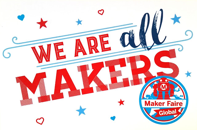"The white landscape postcard has writing in red saying ""We are all makers"" except for the word 'all' which is emphasised in dark blue. The Maker Faire Global logo appear in the bottom right corner. The main message is embellished with light blue flourished rules, stars and love hearts, and red stars and love hearts."