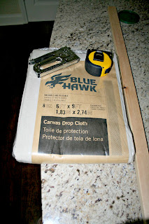 A close up of a staple gun, tape measure, wood trim and canvas drop cloth