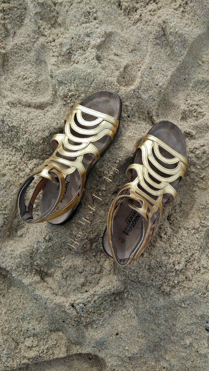naot gold sara sandals on the beach