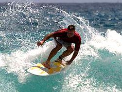 Foto de deportista surfeando en la playa