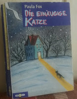 Cover: Eine schwarze Katze läuft durch den Schnee auf ein Haus zu, Licht fällt auf den Schnee