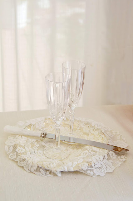 A pair of clear crystal wine glasses with a cake knife, resting on a lace covered plate.