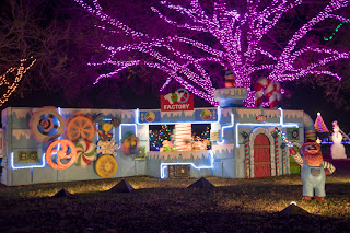 An image of a brightly lit holiday light display featuring a toy factory setup, in Austin, Texas at the Trail of Lights