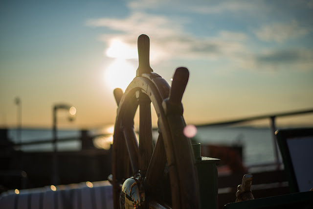 ship's steering wheel in the sunset