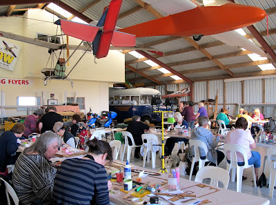 Group of people doing workshops in a hangar, with a bus in the far corner and a plane hanging above them.